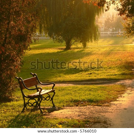 A red bench in the park at sunset - stock photo