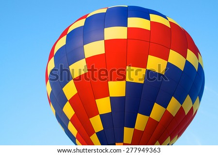 A red, blue, and yellow hot air balloon showing just the top against blue sky. - stock photo