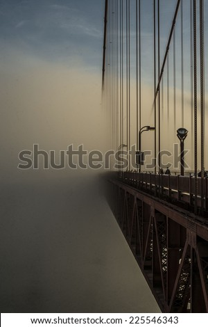 A red bridge extends into a large fog. - stock photo