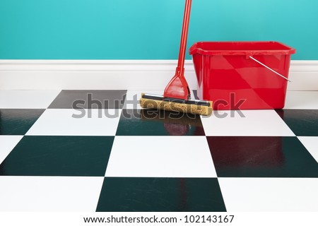 A red bucket and mop on a white and black checkered floor against a turquoise blue wall. - stock photo