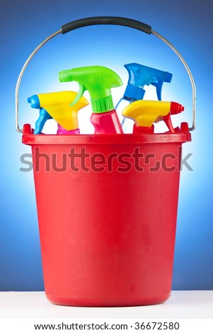 A red bucket filled with assorted cleaning supplies. - stock photo