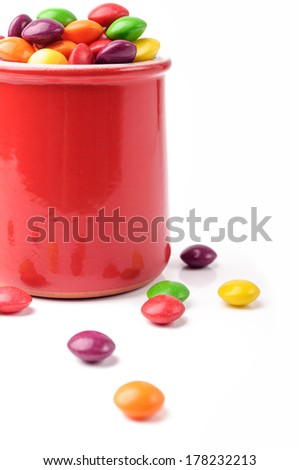 A red ceramic jar with colorful candies - stock photo