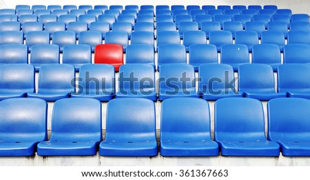 A red chair amidst rows of blue plastic spectator seats.  - stock photo