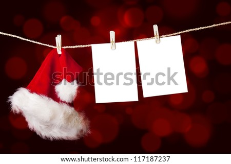 A red christmas Santa hat is hanging on a string together with notes on defocused red lights - stock photo