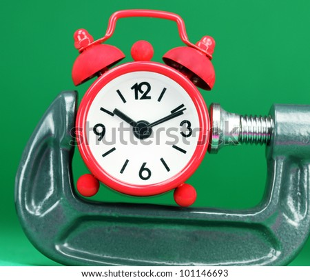 A red colored  alarm clock placed in a Grey clamp against a pastel green background, asking the question do you manage your time effectively. - stock photo