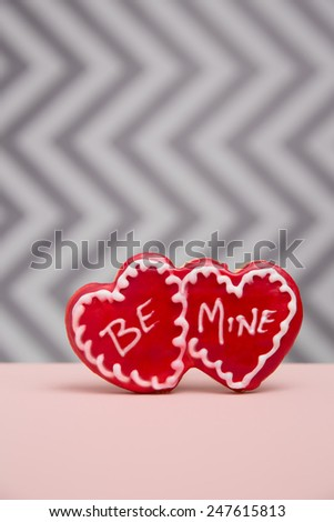 A red Cookie printed with Be Mine on a grey chevron background with pink foreground - stock photo