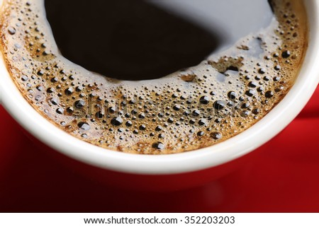 A red cup of tasty coffee, close-up - stock photo