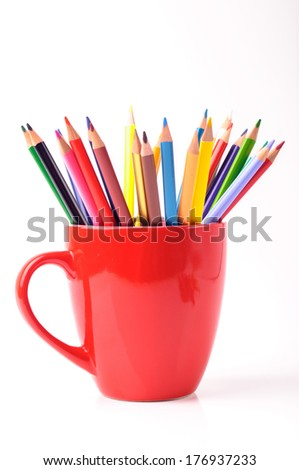 A red cup with color pencils in it - stock photo