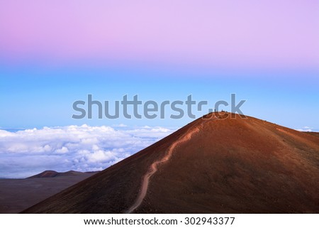 A red dirt mountain with a trail to the top at 14,000 feet overlooks the top of clouds and exposes the pink inversion layer typical of cold air environments.   - stock photo