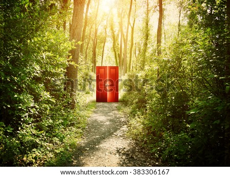 A red doorway is on a trail in the woods with trees for a concept about faith, freedom or opportunity.  - stock photo