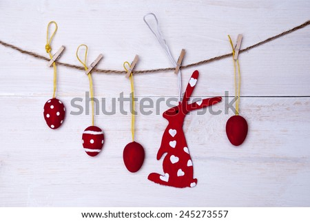A Red Easter Bunny With Hearts Hanging On A Line With Four Red Easter Eggs Which Are Dotted And Striped On White Wooden Vintage Or Rustic Background For Easter Greetings And Happy Easter - stock photo