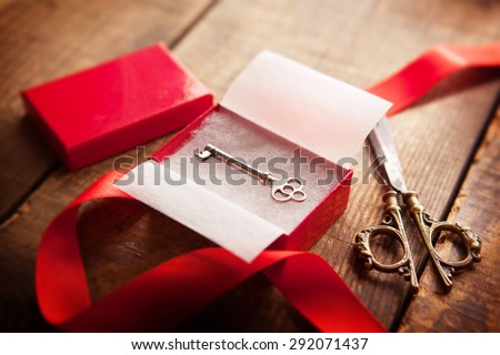 A red gift box with an old, key inside,A red gift box, key,  scissors, and a red ribbon. Focus is on the key. - stock photo