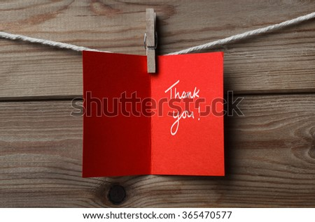 A red greetings card, pegged on to string against wood plank background.  Opened to display the words 'Thank You'. - stock photo