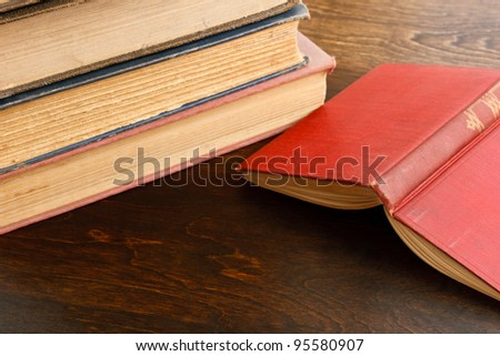 A red hardcover book lies open on a dark wood table with old weathered books in the background - stock photo