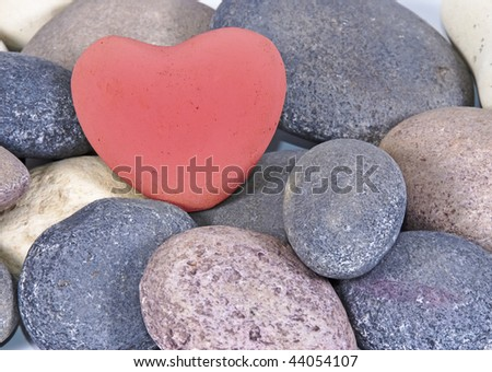 a Red heart of stone between multi colored natural stones - stock photo