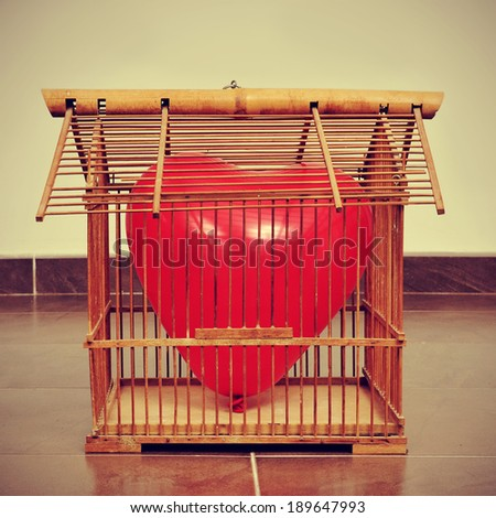 a red heart-shaped balloon in an old birdcage, with a retro effect - stock photo