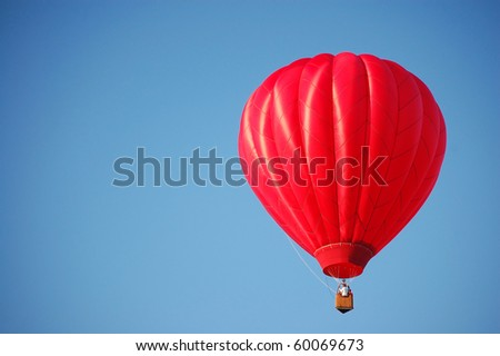 A red hot-air balloon in the sky on a beautiful summer morning. - stock photo