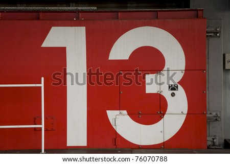 a red japanese tsunami watertight door in osaka bay area with the number 13 painted on it - stock photo