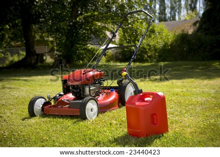 A red lawn mower and gas can in fresh cut grass. - stock photo