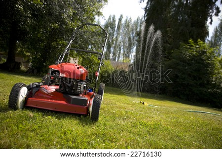 A red lawn mower in fresh cut grass. - stock photo
