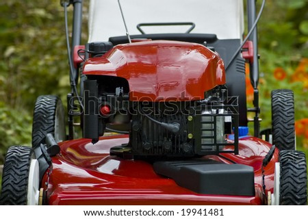 A red lawnmower up close. - stock photo