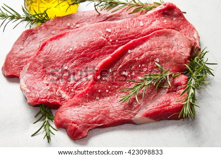 a red meat with rosemary on marble table - stock photo