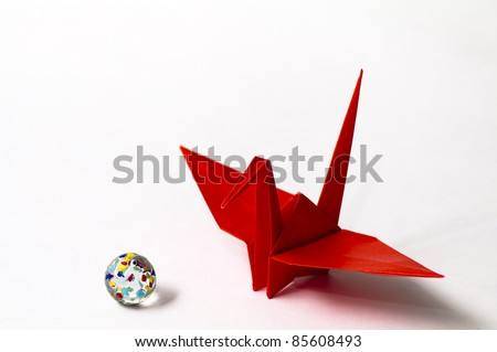 a red paper crane and a marble with white background - stock photo
