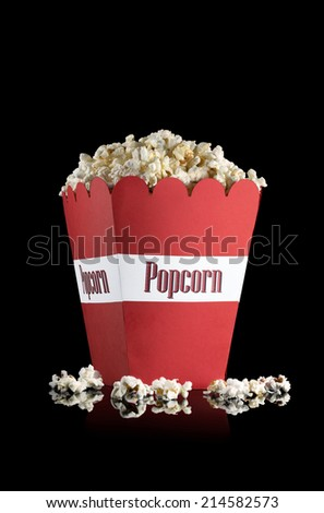 A red paper cup with popcorn against black background with popcorn that has fallen out. - stock photo