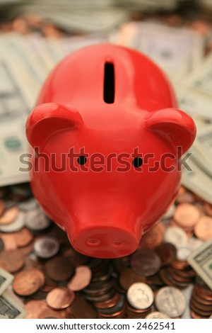 A red piggy back sitting on coins and bills - stock photo