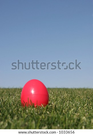 A red plastic Easter egg on the grass with a blue sky - shallow DOF. - stock photo