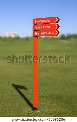 A red pole with sign arrows, pointing directions in a golf course: Driving Range, Putting Green, Short Game Area, over a clear blue sky with a blurred fairway on background - stock photo