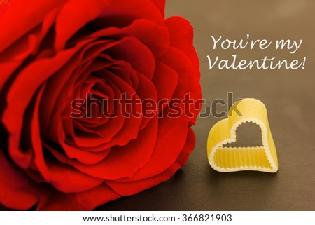 a red rose and a heart against a dark background - stock photo