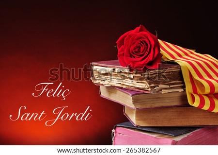 a red rose and the catalan flag on a pile of old books and the text Felic Sant Jordi, Happy Saint Georges Day, written in catalan, when it is tradition to give red roses and books in Catalonia, Spain - stock photo