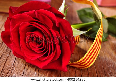 a red rose with the Catalan flag on a rustic wooden table and some old books in the background, for the Saint George Day celebrated in Catalonia, Spain, where is tradition to give roses and books - stock photo