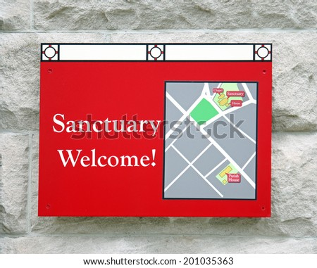 A red sign outside of a church reading  Sanctuary Welcome! - stock photo