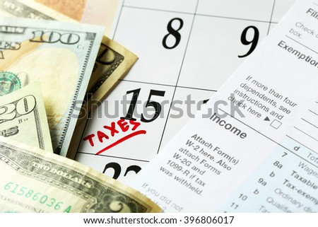 A red tax mark in the calendar, tax form with dollar bills, close up - stock photo