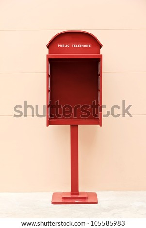 A red telephone box with beautiful pink wall. - stock photo