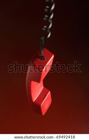 A red telephone receiver hanging on its cord - stock photo