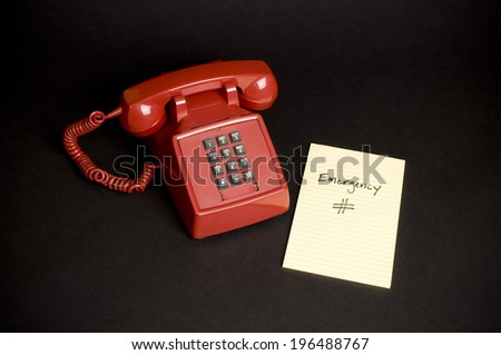 A red telephone with a piece of paper with emergency number written on it. - stock photo