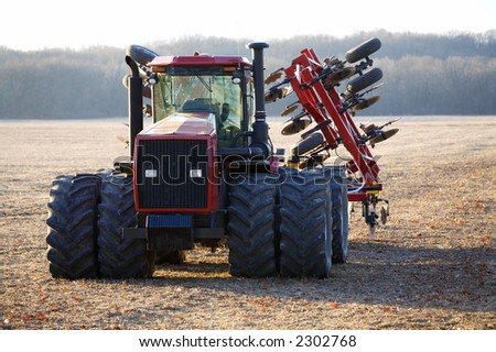 A red tractor in an empty field - stock photo