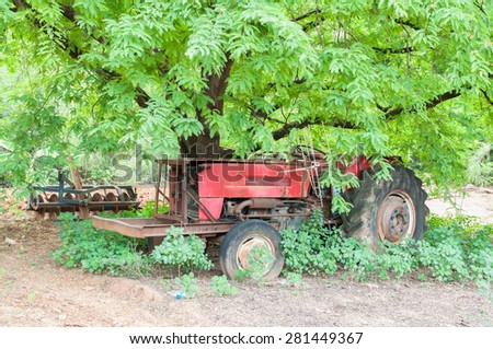 a red tractor under big tree - stock photo