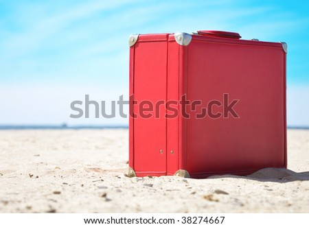 A red travel suitcase is alone on a beach with the lake or ocean in the background. Use this image to represent a voyage, getaway to a  tropical beach vacation in the sun. - stock photo