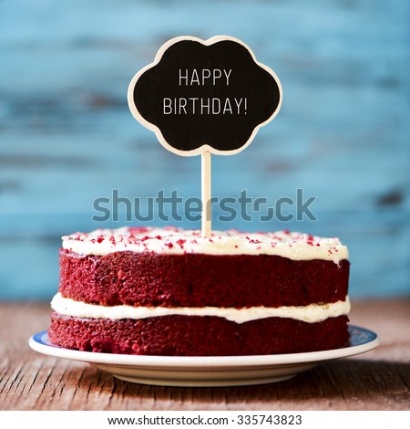 a red velvet cake with a chalkboard in the shape of a thought bubble with the text happy birthday, on a rustic wooden table - stock photo