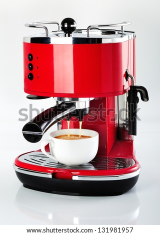 A red vintage looking espresso coffee machine is making a coffee on a white background - stock photo