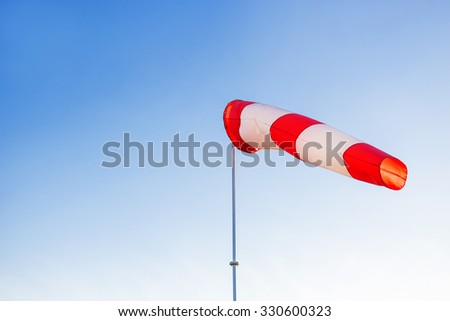 A red wind vane against a clear blue sky. - stock photo