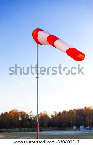 A red wind vane against a clear blue sky in autumn day. - stock photo