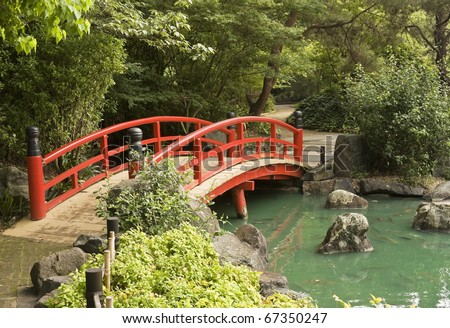 A red wooden bridge over a pond in a Japanese garden - stock photo
