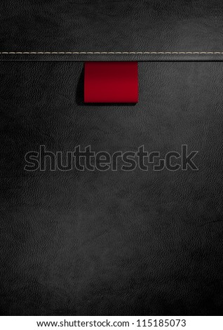 A red woven clothing label sewn into seamed black leather - stock photo