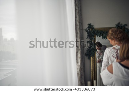 A reflection of gorgeous bride in a mirror while she stands behind a window - stock photo