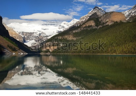 a reflection of the great Rocky Mountains in the waters of Lake Agnes, Banff Alberta, Canada - stock photo